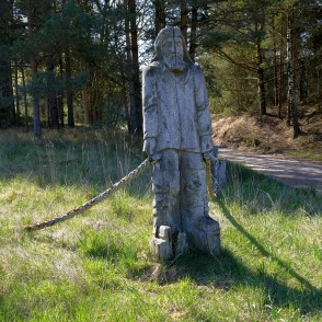 A Wooden Sculpture Walking Along The Pape Trail